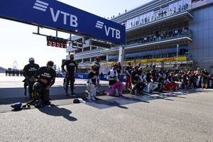 The drivers stand and kneel in support of the End Racism campaign on the grid