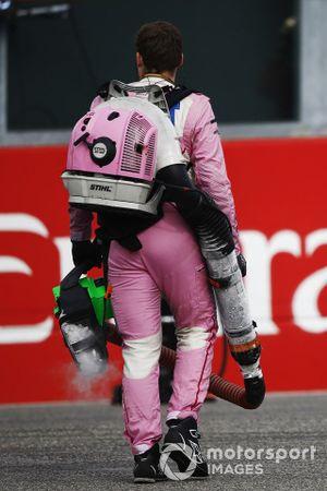 Un membro del team Racing Point porta un soffiatore sulla griglia