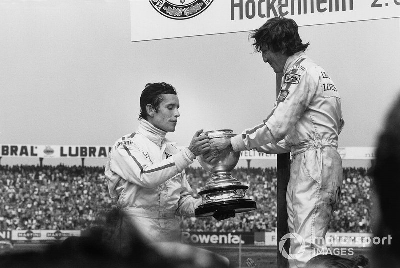 Race winner Jochen Rindt, Lotus, offers the winners trophy filled with Champagne to Jacky Ickx, Ferrari, 2nd position