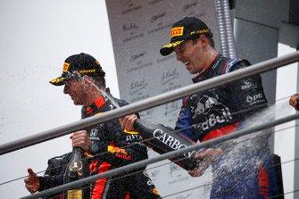 Le vainqueur Max Verstappen, Red Bull Racing, et le troisième, Daniil Kvyat, Toro Rosso, avec du champagne sur le podium