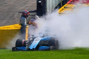 Robert Kubica, Williams Racing FW42, helps a marshal extinguish the fire