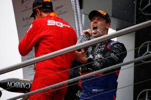 Sebastian Vettel, Ferrari, 2nd position, and Daniil Kvyat, Toro Rosso, 3rd position, celebrate on the podium