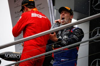 Sebastian Vettel, Ferrari, 2nd position, and Daniil Kvyat, Toro Rosso, 3rd position, celebrate on the podium