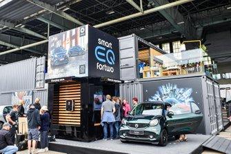 Merecedes stand con una Smart car, charging point