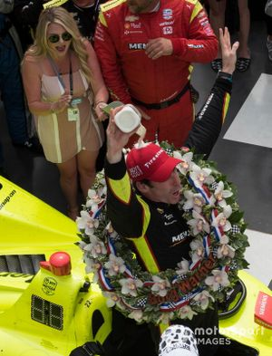 Simon Pagenaud, Team Penske Chevrolet, pours milk over his head in victory lane