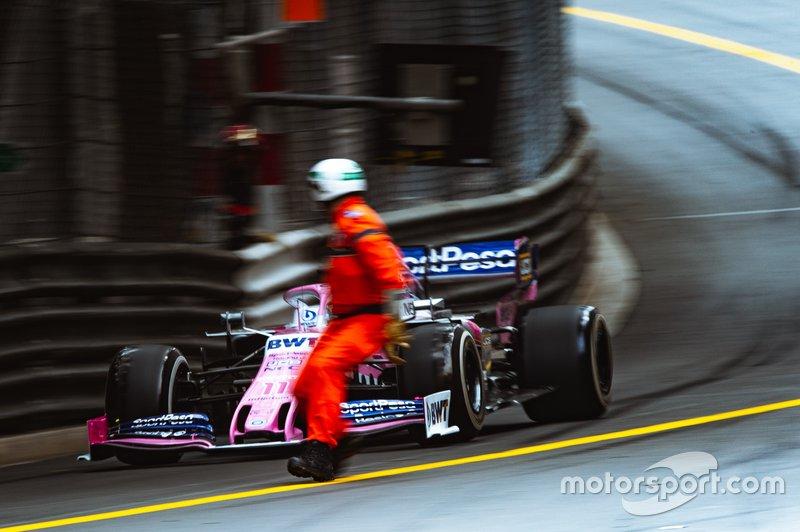 Un comisario cruza la pista por delante del coche de Sergio Pérez