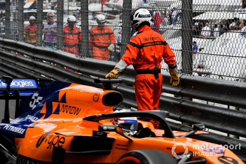 Carlos Sainz Jr., McLaren MCL34 drives past a Marshal on track