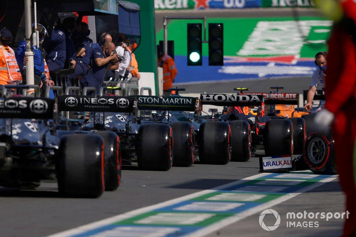 Lance Stroll, Aston Martin AMR21, y Valtteri Bottas, Mercedes W12, en el pit lane