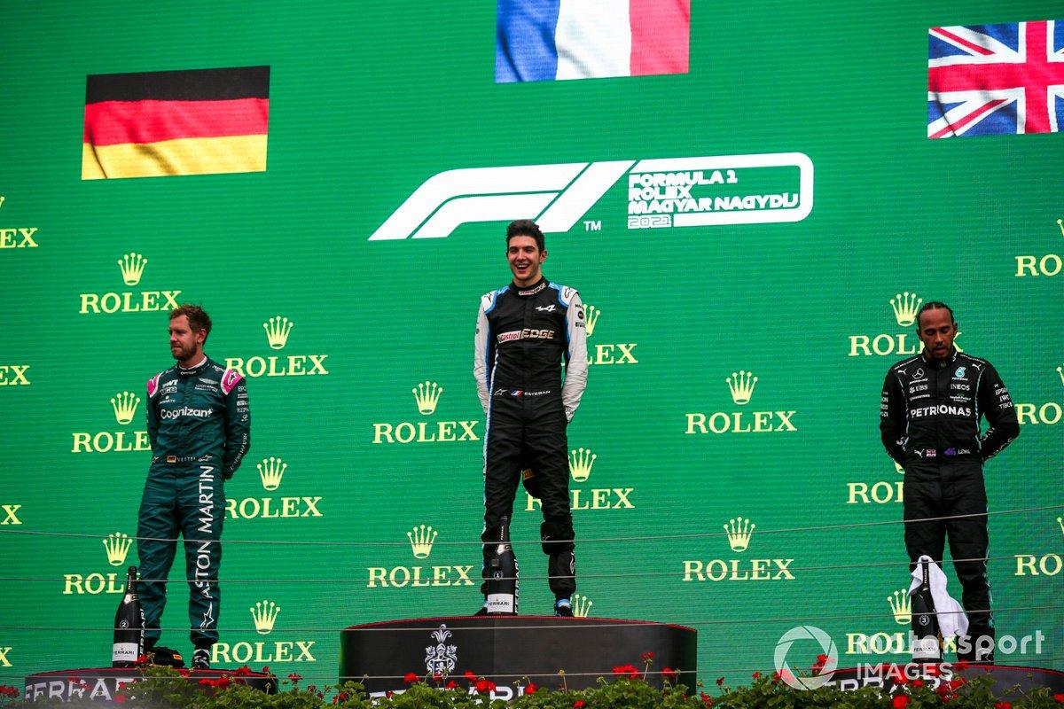 Sebastian Vettel, Aston Martin, secondo classificato, Esteban Ocon, Alpine F1, primo classificato, e Lewis Hamilton, Mercedes, terzo classificato, sul podio
