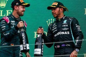 Le deuxième Sebastian Vettel, Aston Martin, et le troisième Lewis Hamilton, Mercedes, se félicitent sur le podium