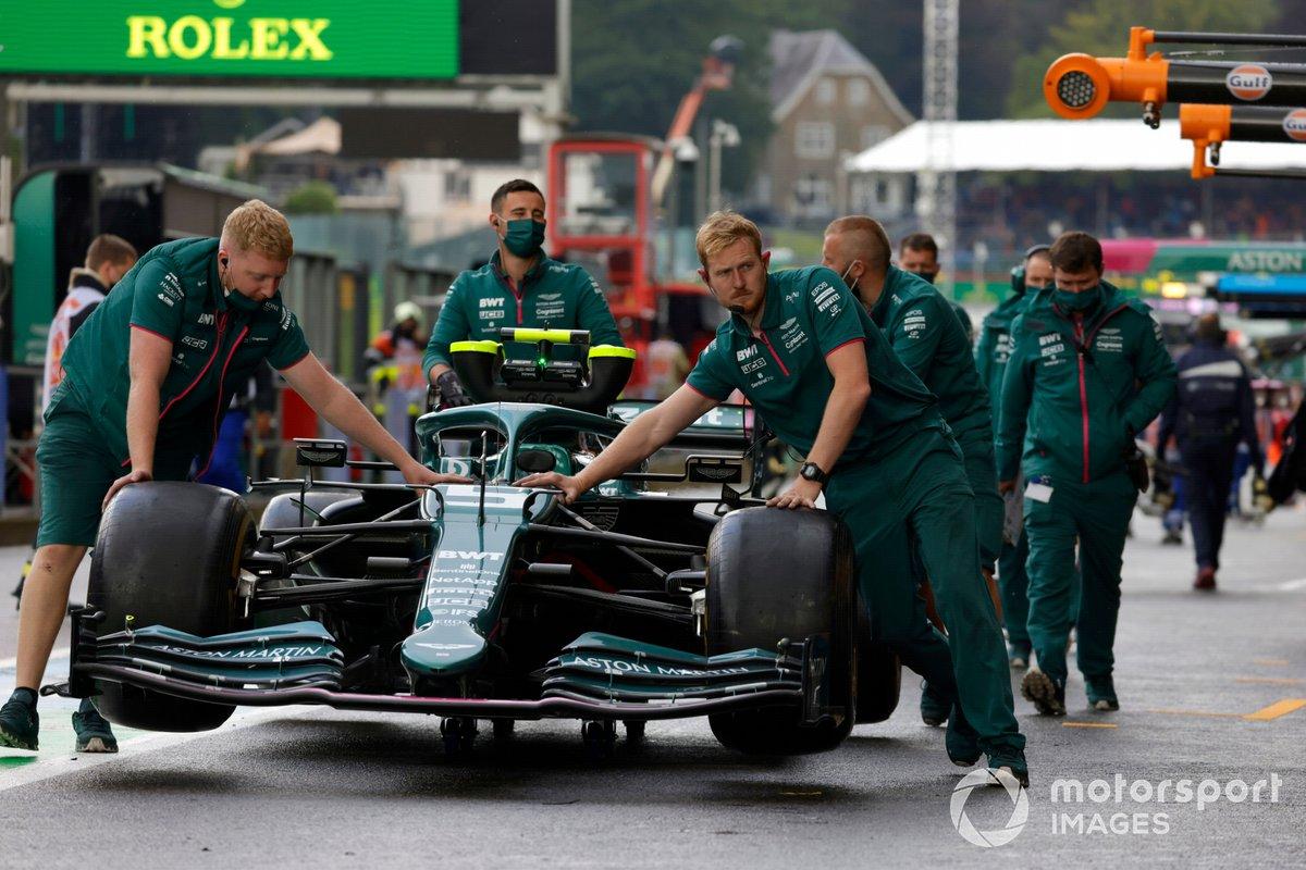 Los mecánicos mueven el coche de Sebastian Vettel, Aston Martin AMR21, en el pit lane