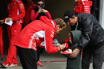 Sebastian Vettel, Ferrari signs an autograph for a young fan