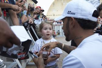 Lewis Hamilton, Mercedes AMG F1, partage un biscuit avec une jeune fan