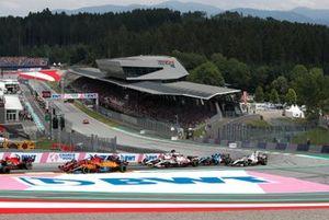 Daniel Ricciardo, McLaren MCL35M, Charles Leclerc, Ferrari SF21, Kimi Raikkonen, Alfa Romeo Racing C41, and the remainder of the field on the opening lap