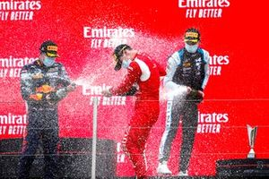 Dennis Hauger, Prema Racing, 2nd position, Arthur Leclerc, Prema Racing, 1st position, and Victor Martins, MP Motorsport, 3rd position, celebrate on the podium with Champagne