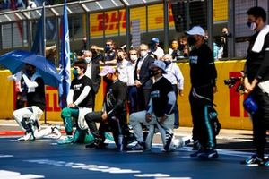 The drivers stand and take a knee on the grid in support of the End Racism campaign