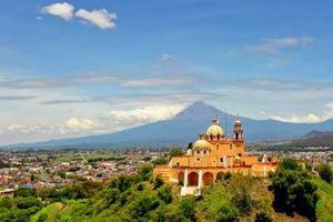 Santuario de la Virgen de los Remedios church with the active volcano Popocatepetl behind in Cholula, Puebla, Mexico