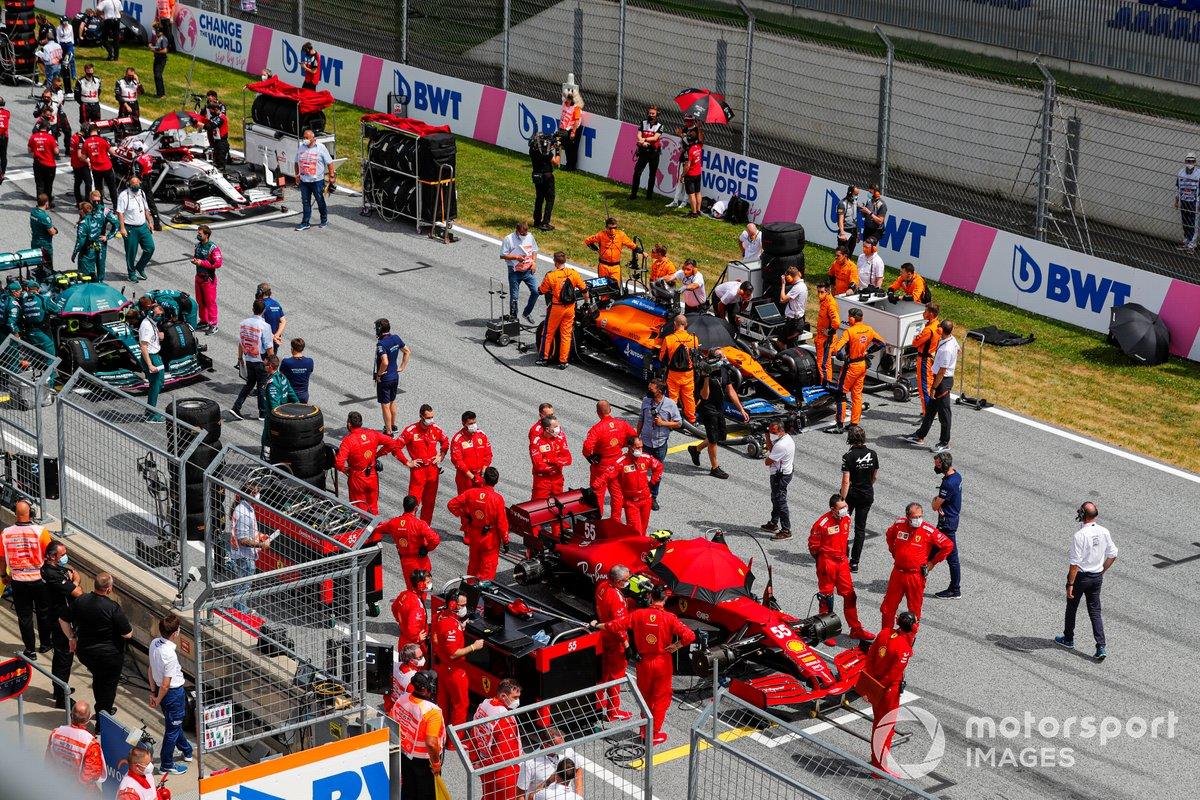Mecánicos en la parrilla con Carlos Sainz Jr., Ferrari SF21, y Daniel Ricciardo, McLaren MCL35M