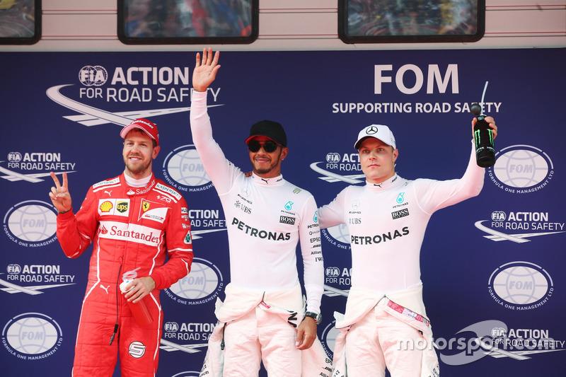 Lewis Hamilton, Mercedes AMG, celebrates taking pole position alongside Sebastian Vettel, Ferrari and Valtteri Bottas, Mercedes AMG