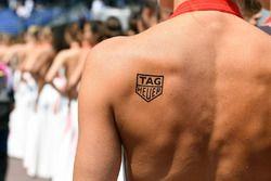 Chica de la parrilla con un tatuaje de Tag Heuer
