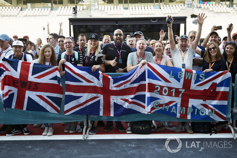 Fans of Lewis Hamilton, Mercedes AMG F1, wait outside the garage in the pit lane