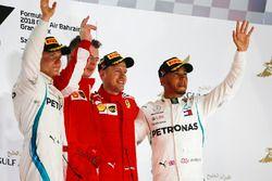 Valtteri Bottas, Mercedes AMG F1, 2nd position, Sebastian Vettel, Ferrari, 1st position, and Lewis Hamilton, Mercedes AMG F1, 3rd position, on the podium with the Ferrari Constructors trophy delegate