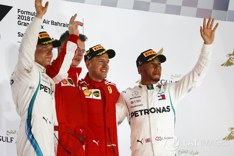 Valtteri Bottas, Mercedes AMG F1, 2nd position, Sebastian Vettel, Ferrari, 1st position, and Lewis Hamilton, Mercedes AMG F1, 3rd position, on the podium with the Ferrari Constructors trophy delegate