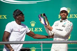 Usain Bolt presents a pair of his running shoes to Race winner Lewis Hamilton, Mercedes AMG F1, on the podium