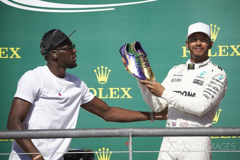 Usain Bolt le regala un par de zapatillas de atletismo al ganador de la carrera de Austin, Lewis Hamilton, Mercedes AMG F1, en el podio