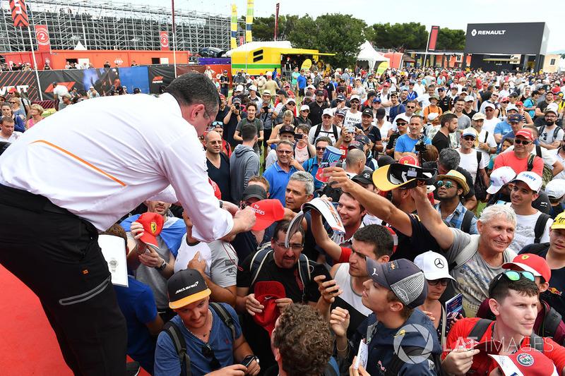 Éric Boullier, directeur de la compétition de McLaren, signe des autographes pour les fans
