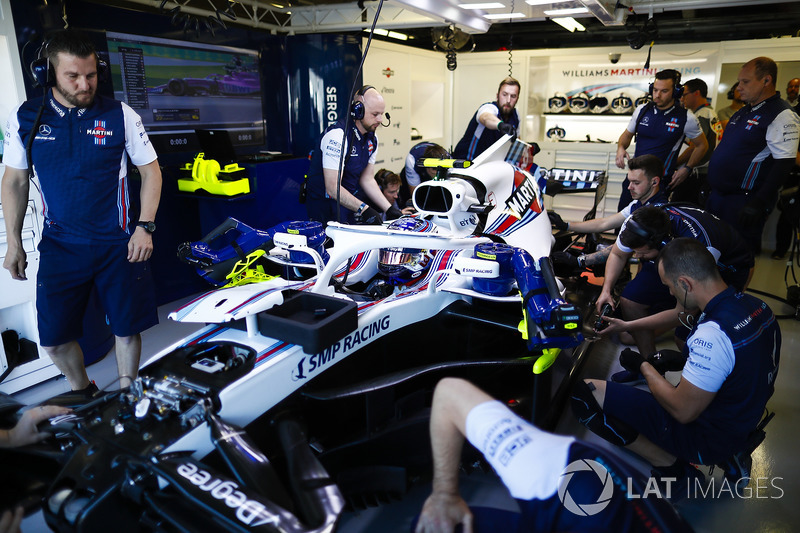 Mechanics work on the Lance Stroll Williams FW41 in the team's garage