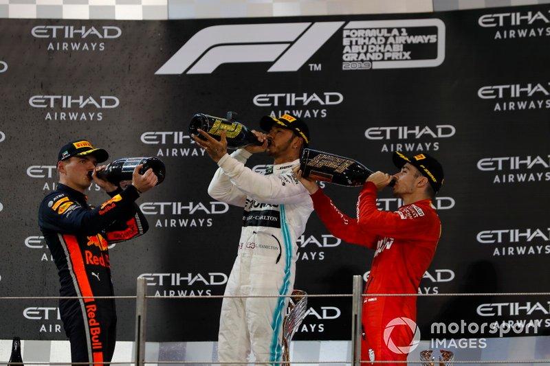 Max Verstappen, Red Bull Racing, secondo classificato, Lewis Hamilton, Mercedes AMG F1, primo classificato, e Charles Leclerc, Ferrari, terzo classificato, festeggiano sul podio con lo champagne