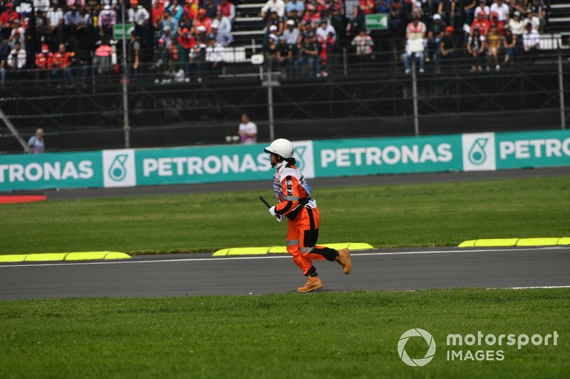 A marshal retrieves some debris from the track