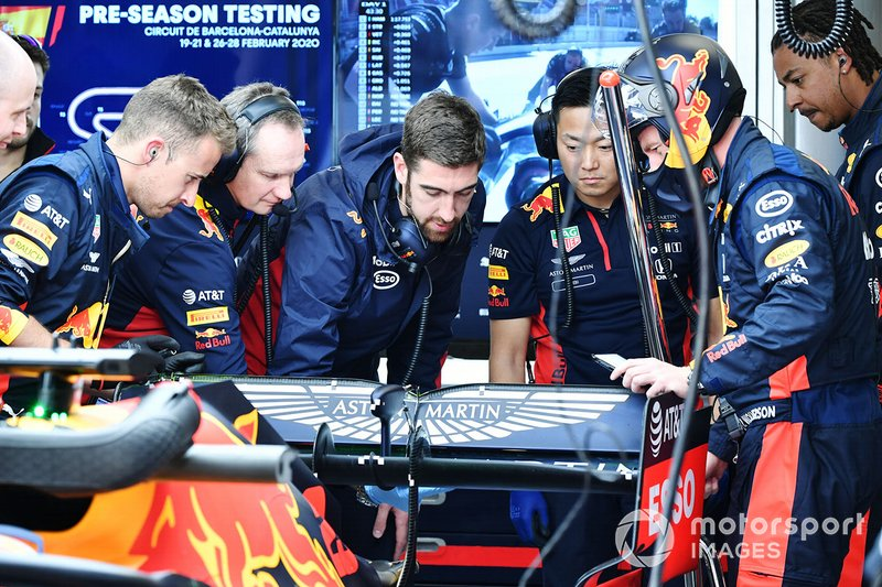Red Bull team members examine the rear of a Red Bull Racing RB16