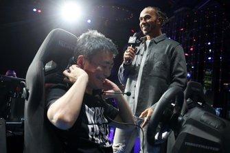 Formula 1 Driver, Lewis Hamilton looks on as producer of Gran Turismo, Kazunori Yamauchi gives a demonstration