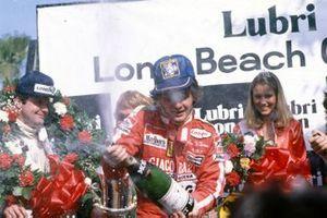 Gilles Villeneuve, Ferrari celebrates victory on the podium with third place Alan Jones, Williams