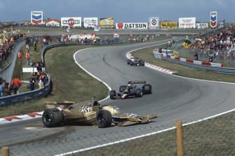 Mario Andretti and Ronnie Peterson, Lotus 78 Ford pass the crashed car of Riccardo Patrese, Arrows A1-Ford Cosworth