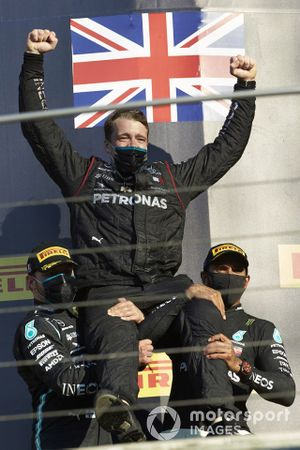 Valtteri Bottas, Mercedes-AMG F1, 2nd position, and Lewis Hamilton, Mercedes-AMG F1, 1st position, lift up a team member on the podium