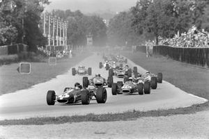 Dan Gurney, Eagle T1G Weslake, leads Jack Brabham, Brabham BT24 Repco, Graham Hill, Lotus 49 Ford, Bruce McLaren, McLaren M5A BRM, and the rest of the field on the opening lap
