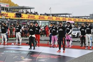 The drivers stand on the grid for the national anthem prior to the start