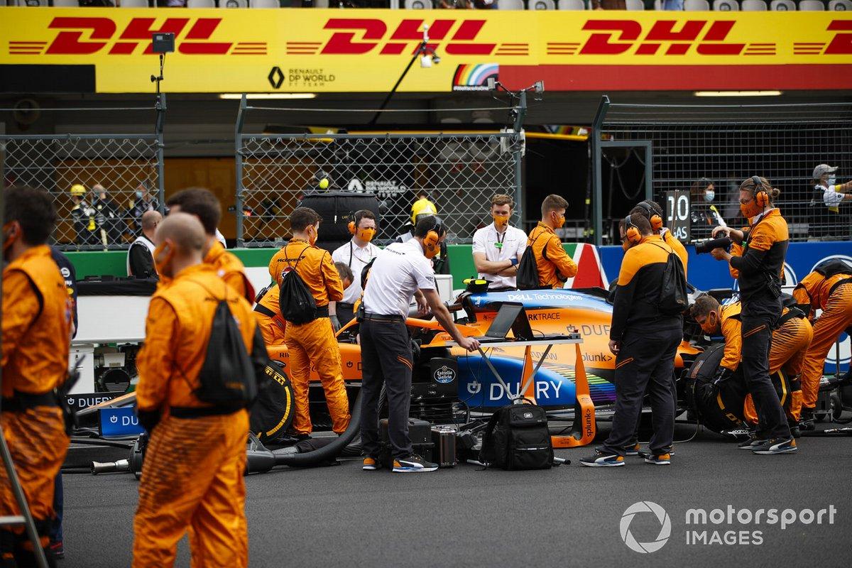 Mecánicos en la parrilla con el coche de Lando Norris, McLaren MCL35