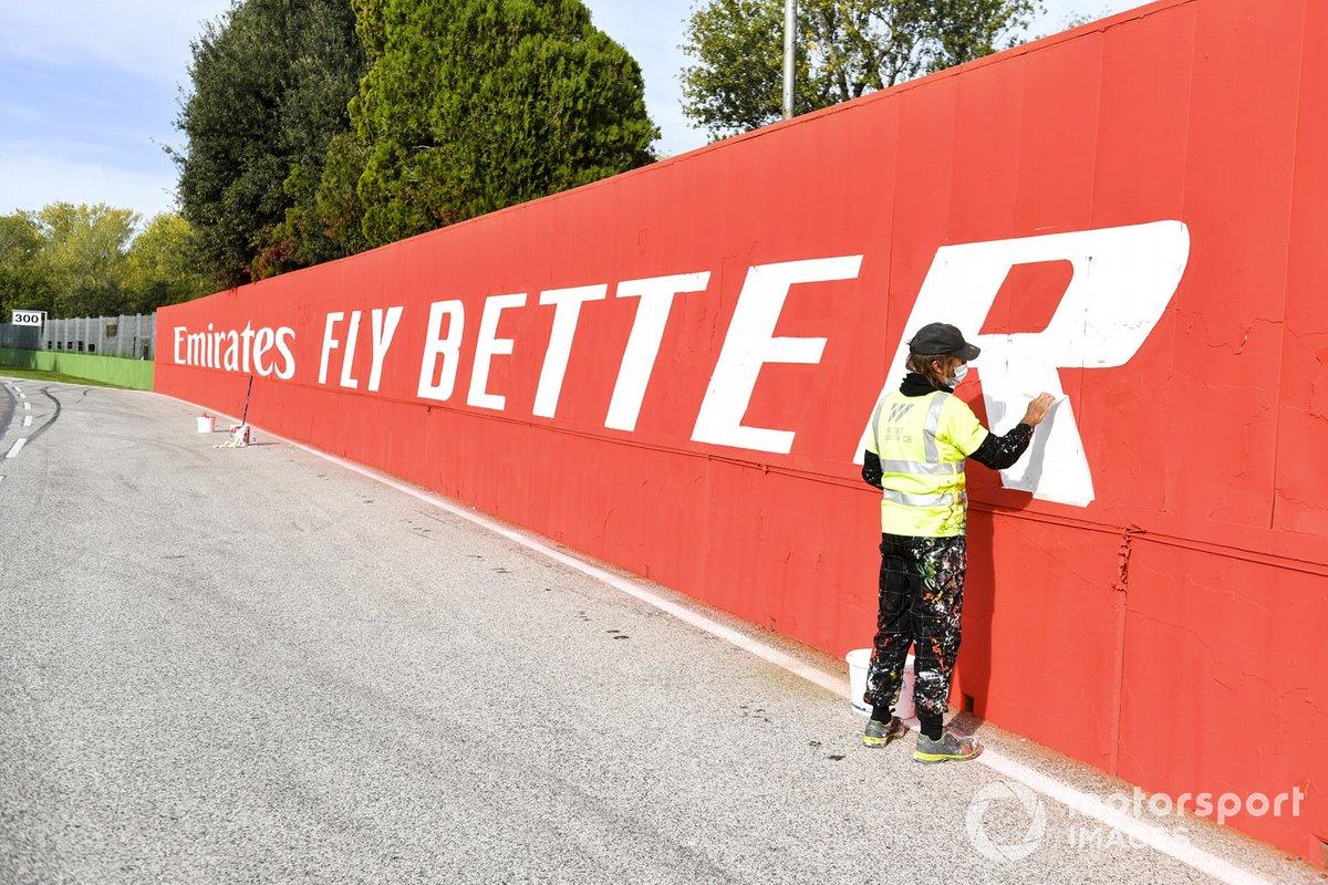 Un pintor retoca carteles de patrocinadores