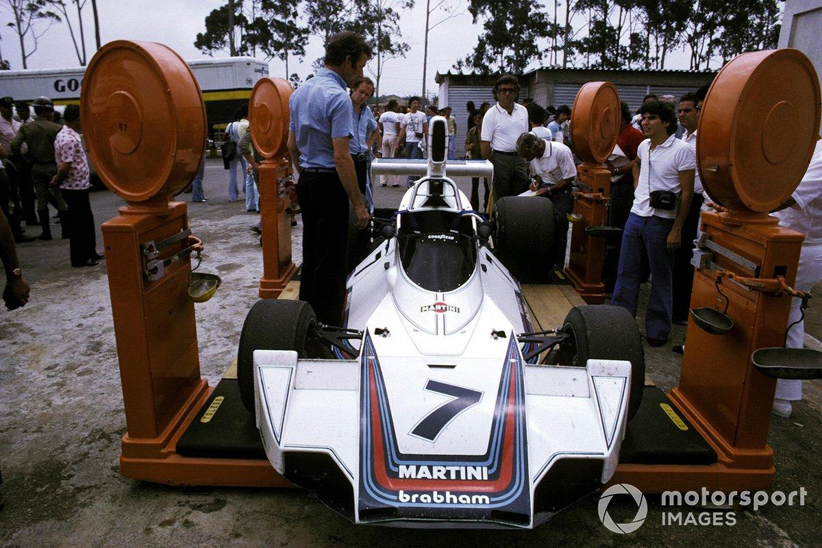 Un joven Nelson Piquet mira como el Brabham BT44B octavo lugar de Carlos Reutemann es pesado en el área del paddock