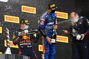 Max Verstappen, Red Bull Racing, 1st position, Lando Norris, McLaren, 3rd position, and the Red Bull trophy delegate battle with Chamapagne on the podium