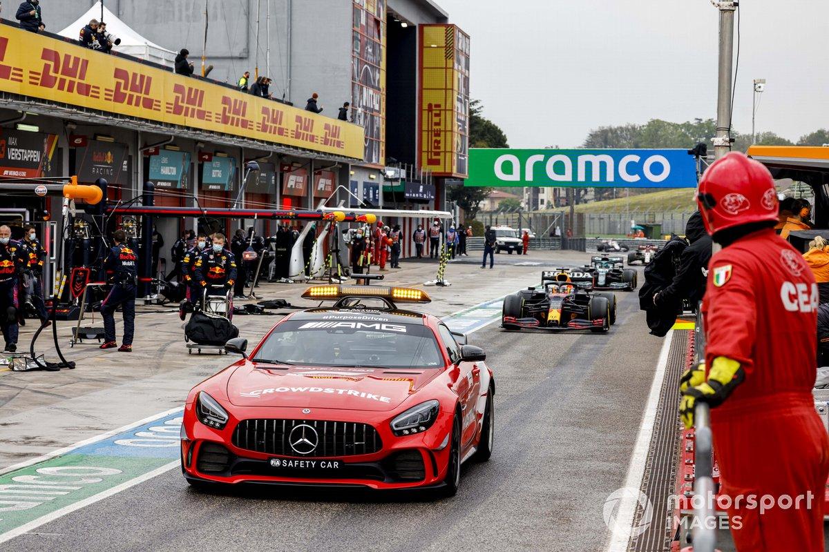 El Safety Car lidera a Max Verstappen, Red Bull Racing RB16B, Lance Stroll, Aston Martin AMR21, y el resto del campo en los pits