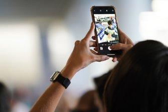 A fan takes a photo of Sérgio Jimenez, Jaguar Brazil Racing on their phone