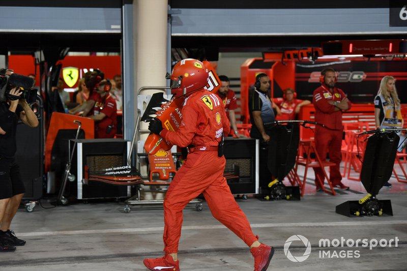 Un miembro del equipo de boxes de Ferrari con el morro dañado del coche de Sebastian Vettel, Ferrari SF90