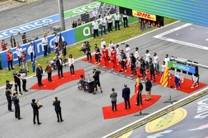 The drivers, officials and dignitaries stand in line on the grid for the national anthem prior to the start