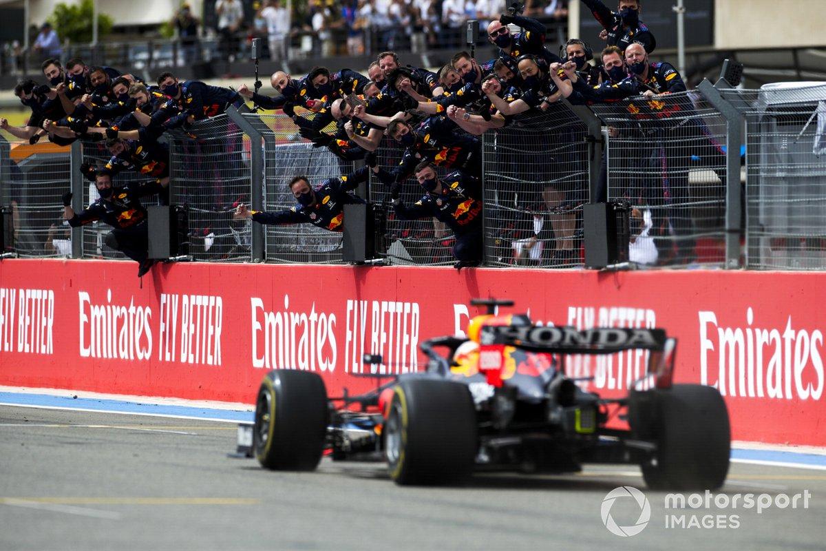 Max Verstappen, Red Bull Racing RB16B, 1° classificato, taglia il traguardo per la gioia della sua squadra al muretto dei box