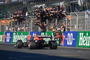 Max Verstappen, Red Bull Racing RB16B, 1e plaats, passeert zijn opgetogen team op de pitmuur na het overschrijden van de lijn